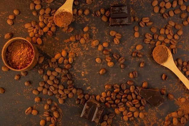 Uma vista superior sementes de café marrom com barras de chocolate em todo o grânulo de grão de semente de café de fundo marrom Foto gratuita