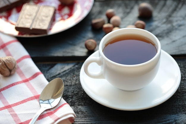 Uma xícara branca de chá com barra de chocolate e nozes ao redor. Foto gratuita