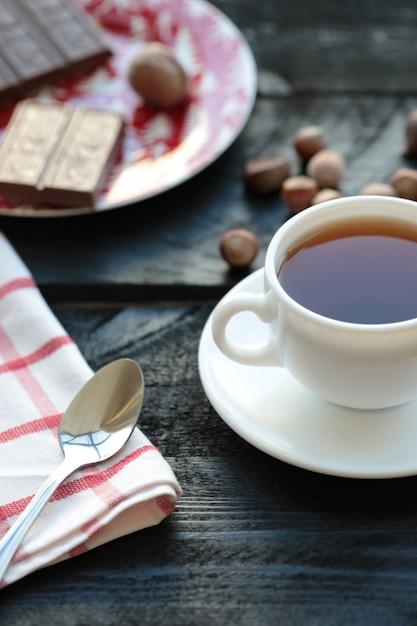 Uma xícara branca de chá com barra de chocolate na mesa de madeira. Foto gratuita