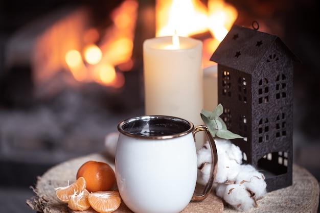 Uma xícara com elementos decorativos em um toco de madeira perto da lareira. o conceito de férias numa aldeia fora da cidade. Foto gratuita