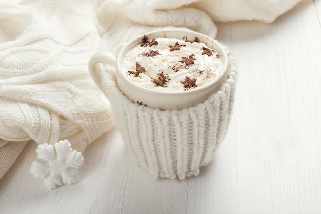 Uma xícara de bebida quente de inverno com chantilly em uma mesa de madeira Foto Premium