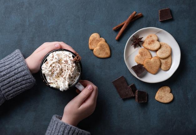 Uma xícara de café com creme e gotas de chocolate na mão da mulher sobre uma mesa escura com biscoitos caseiros, chocolate e canela. vista do topo Foto Premium