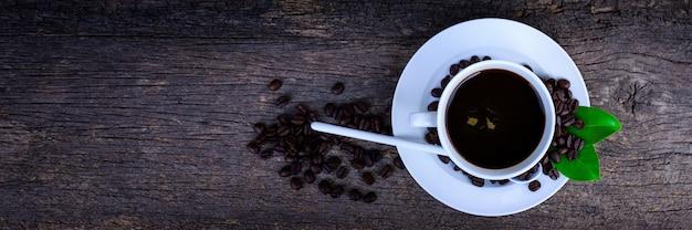 Uma xícara de café com feijões e folhas na madeira preta. vista superior. Foto Premium