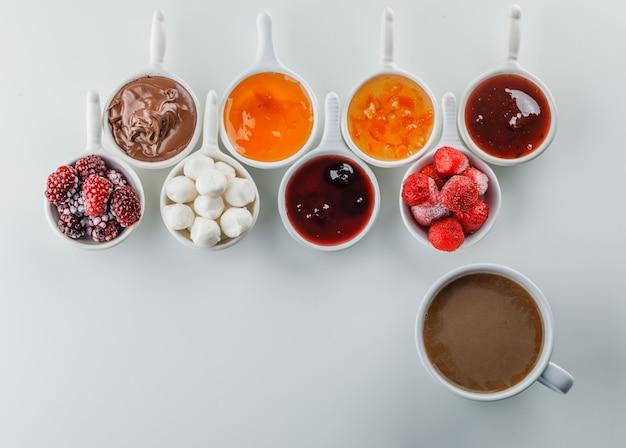 Uma xícara de café com geléias, framboesa, açúcar, chocolate em copos vista superior sobre uma superfície branca Foto gratuita