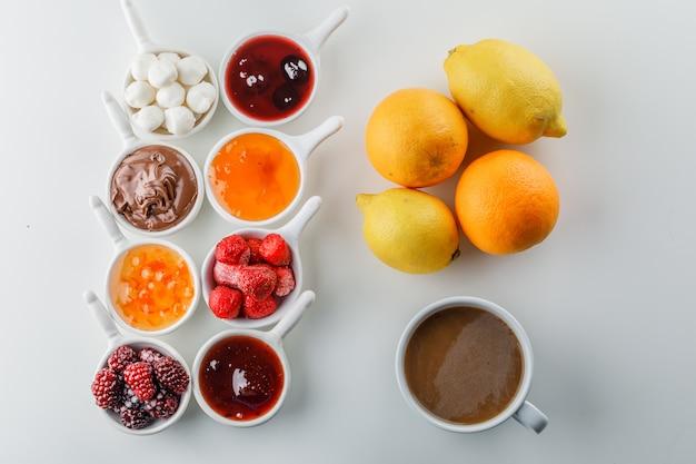 Uma xícara de café com geléias, framboesa, açúcar, chocolate em xícaras, laranja e limão Foto gratuita