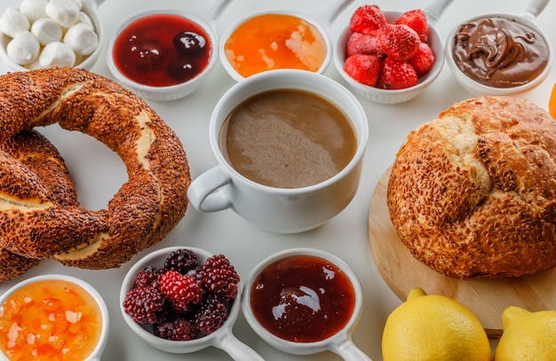 Uma xícara de café com geléias, framboesa, açúcar, chocolate em xícaras, pão turco, pão, laranja e limão Foto gratuita