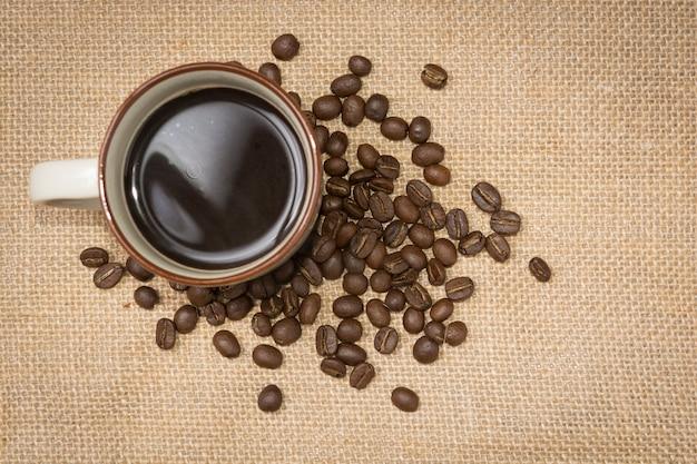Uma xícara de café com grãos de café no saco de cânhamo, vista superior Foto Premium
