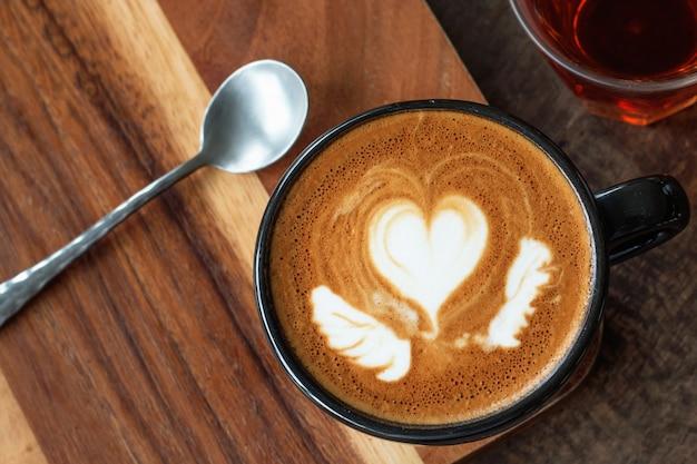 Uma xícara de café com leite quente arte em fundo de madeira Foto Premium