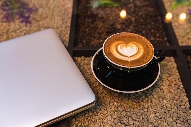 Uma xícara de café de latte art com o computador portátil na mesa com grãos de café Foto Premium