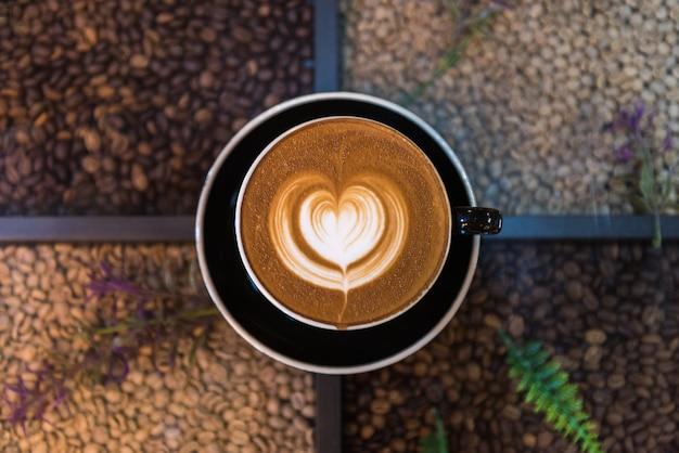 Uma xícara de café de latte art na mesa com origens de grãos de café Foto Premium