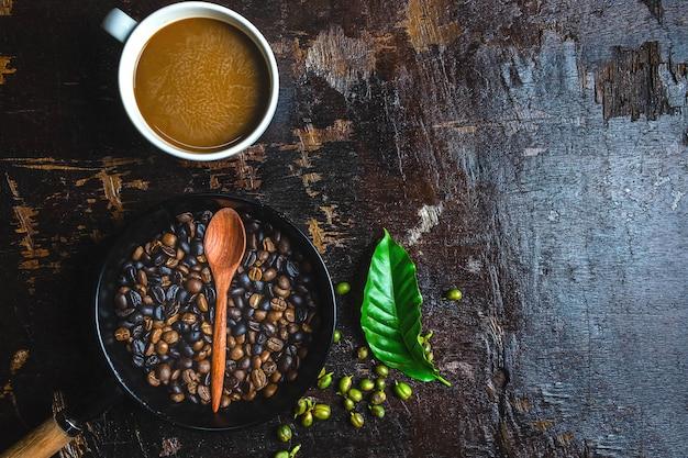 Uma xícara de café e grãos de café em uma mesa de madeira Foto Premium