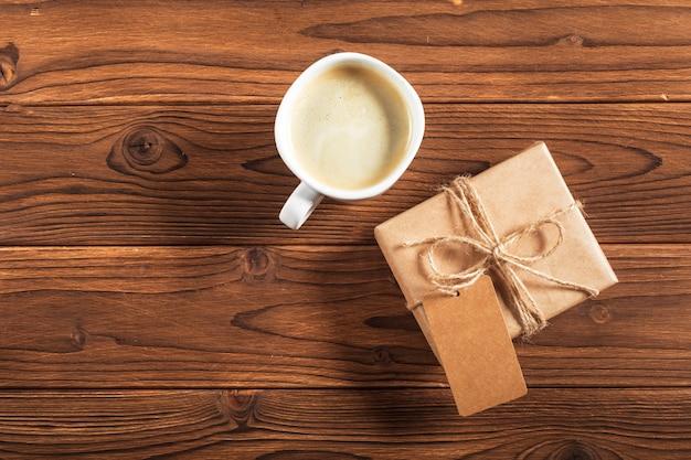 Uma xícara de café e um presente embrulhado em uma mesa de madeira Foto Premium