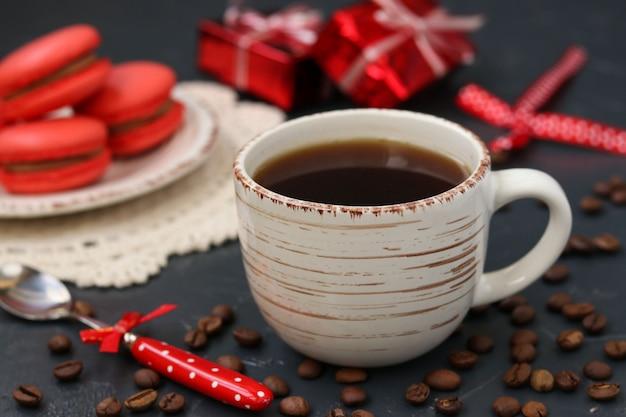 Uma xícara de café em um fundo escuro com confeitos de cor coral Foto Premium