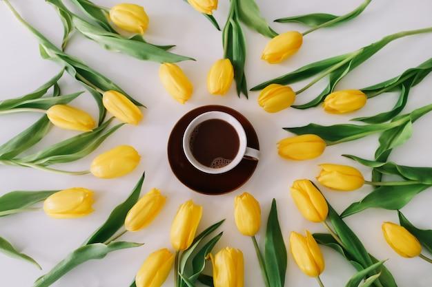 Uma xícara de café em uma moldura de tulipas amarelas em branco. Foto Premium