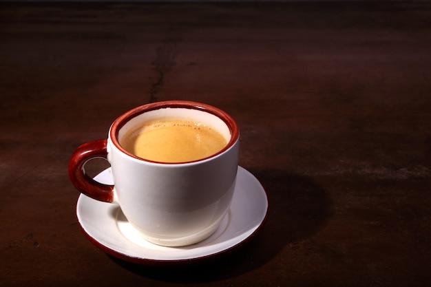 Uma xícara de café expresso em um fundo escuro de madeira Foto Premium