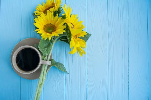 Uma xícara de café, grãos de café, canela e girassol em um fundo azul. clima de verão. Foto Premium
