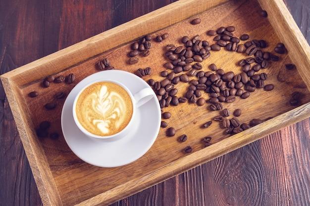 Uma xícara de café latte art e grãos de café próximos em uma caixa de madeira sobre uma mesa de madeira escura. Foto Premium