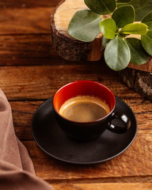 Uma xícara de café meio vazio dentro de uma xícara preta na mesa de madeira marrom bebe café líquido Foto gratuita