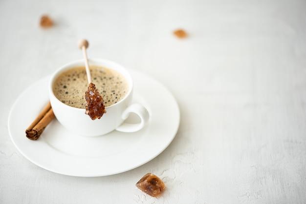 Uma xícara de café preto com canela e açúcar caramelizado no palito, sobre uma mesa branca Foto Premium