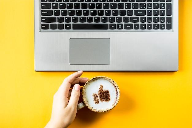 Uma xícara de cappuccino em que é desenhado um sorriso como um polegar para cima Foto Premium