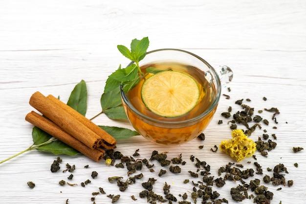 Uma xícara de chá com limão e hortelã e canela em branco, chá de sobremesa Foto gratuita