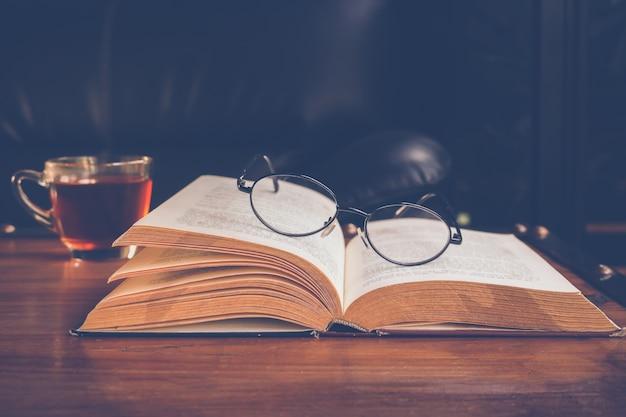 Uma xícara de chá com livro e óculos de leitura Foto Premium