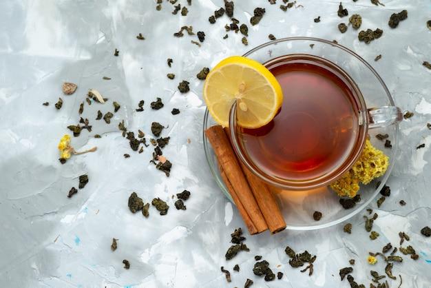 Uma xícara de chá com uma fatia de limão e canela na cobertura, beba frutas líquidas Foto gratuita