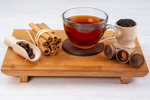 Uma xícara de chá de vista frontal com canela e chifres em um doce de sobremesa de chá de madeira marrom Foto gratuita