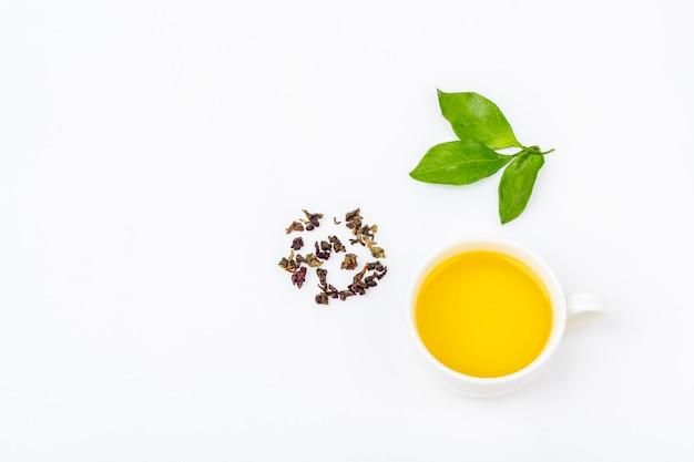 Uma xícara de chá oolong com folhas frescas e um montão de chá verde seco em um fundo branco, com espaço de cópia para o texto. ervas orgânicas, chá asiático verde para a cerimônia do chá. configuração plana Foto Premium
