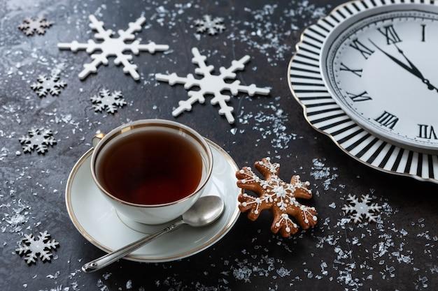 Uma xícara de chá, pão de gengibre e um relógio com flechas. fundo de natal Foto Premium