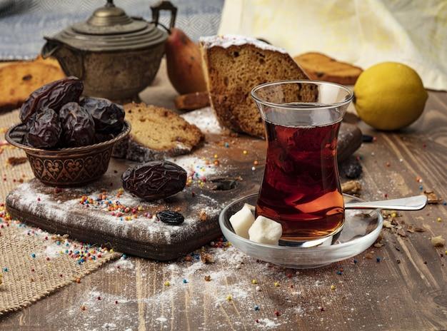Uma xícara de chá quente com datas em fundo de madeira. Foto Premium