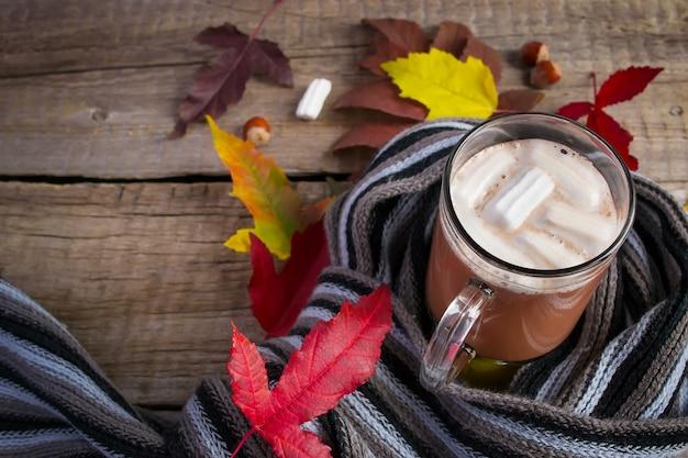 Uma xícara de chocolate com marshmallows, envolto lenço macio e outono Foto Premium