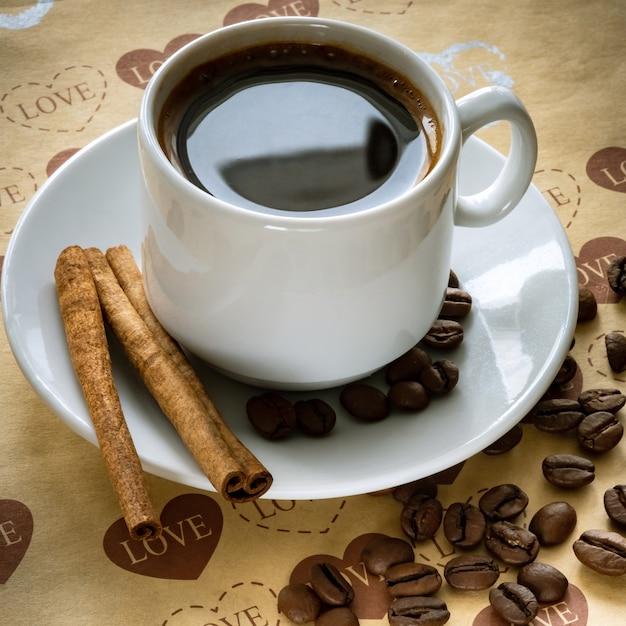 Uma xícara de grãos de café naturais e canela Foto Premium