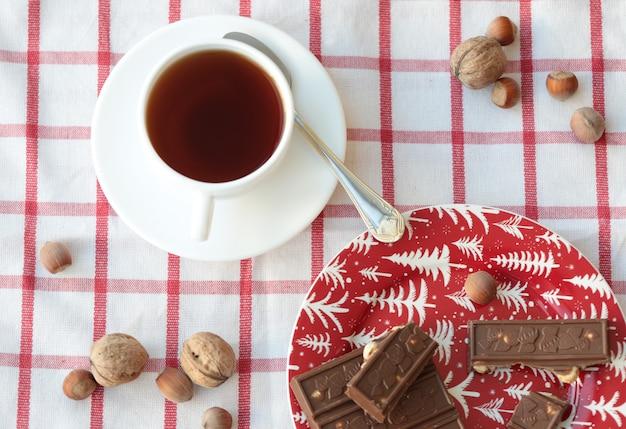 Uma xícara de pedaços de chá e chocolate no prato vermelho. Foto gratuita