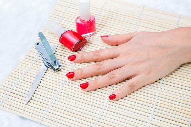 Unhas de mulher bonita manicured com esmalte vermelho Foto Premium