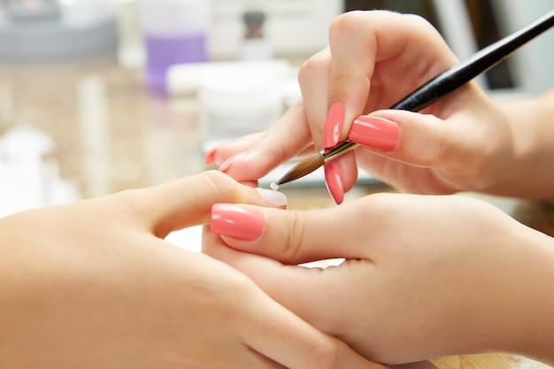 Unhas pintando mulher com escova no salão de beleza Foto Premium