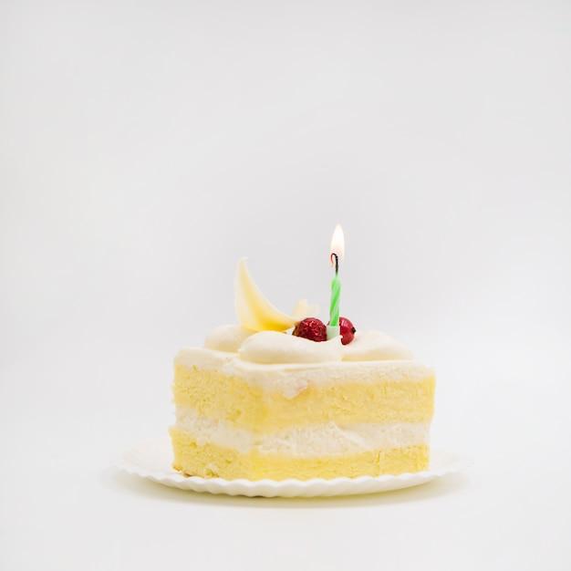 Única vela sobre a fatia de bolo contra o fundo branco Foto gratuita