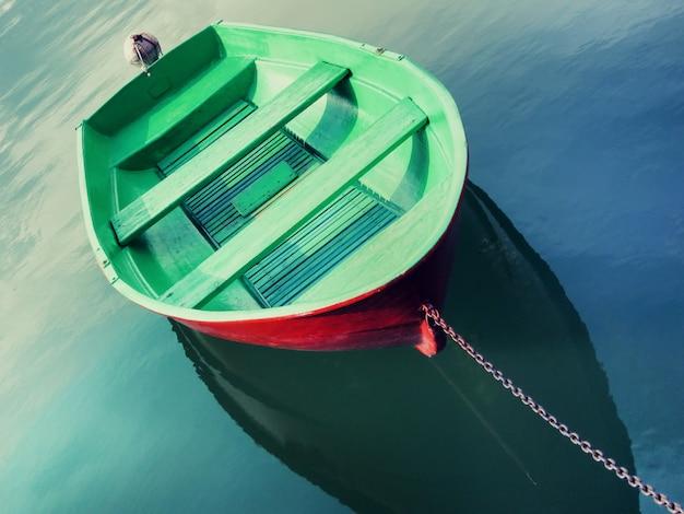 Único barco de pesca pintado em verde flutuando na água e amarrado com corrente metálica Foto Premium