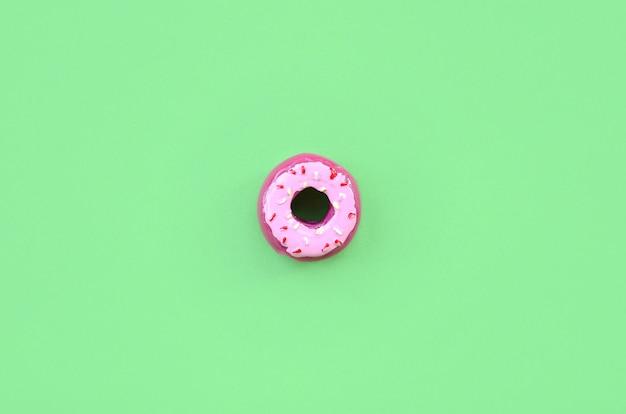 Único pequeno donut de plástico encontra-se em um fundo colorido pastel Foto Premium