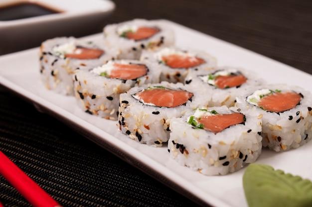 Uramaki japonês de salmão um arroz com legumes, comida asiática, refrescante e deliciosa comida de peixe, frutos do mar, alimentos orgânicos Foto Premium
