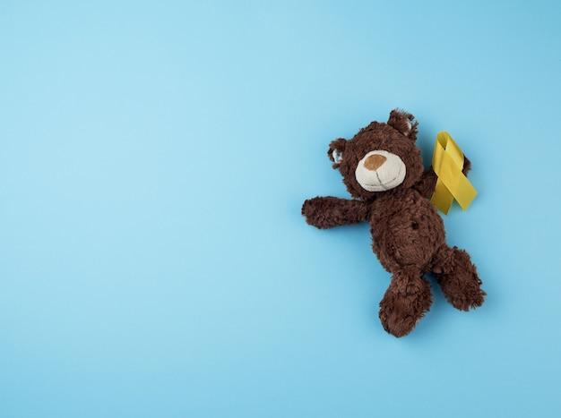Ursinho marrom tem na pata uma fita amarela dobrada em um loop Foto Premium