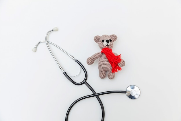 Urso de brinquedo de design simplesmente simples e estetoscópio de equipamento de medicina isolado Foto Premium