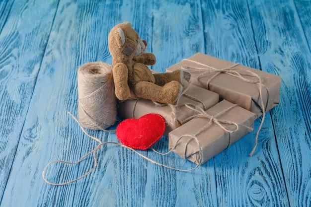 Urso de brinquedo e alguns pacotes de papel embrulhados na mesa de madeira Foto Premium