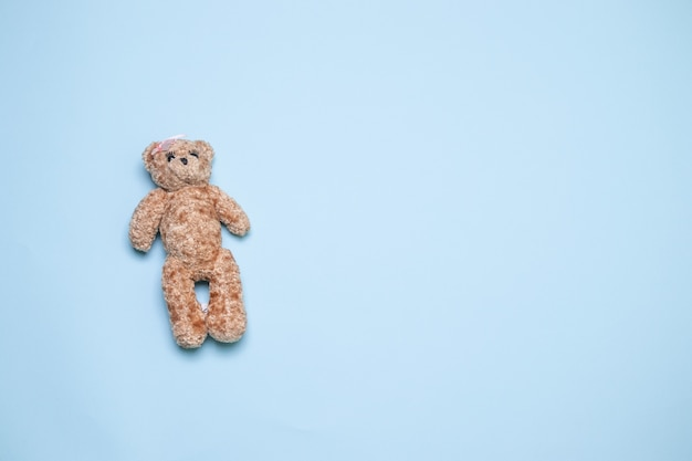 Urso de brinquedo sobre o fundo azul com vista superior do espaço da cópia, configuração plana Foto Premium