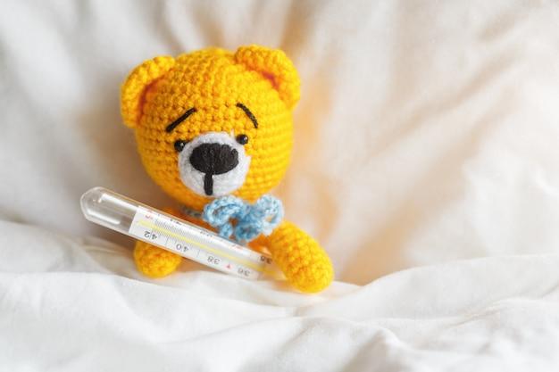 Urso de peluche doente amarelo com o termômetro no quarto branco. Foto Premium