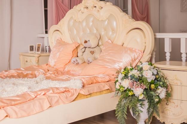 Urso de peluche que senta-se na cama branca no quarto acolhedor e claro. Foto Premium