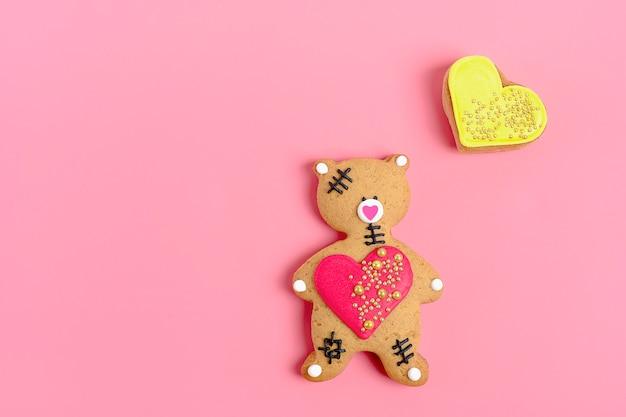 Urso de peluche romântico, coração do pão-de-espécie no fundo cor-de-rosa na moda. Foto Premium