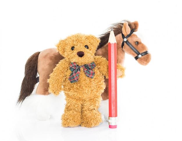 Urso de pelúcia com lápis vermelho e cavalos Foto Premium