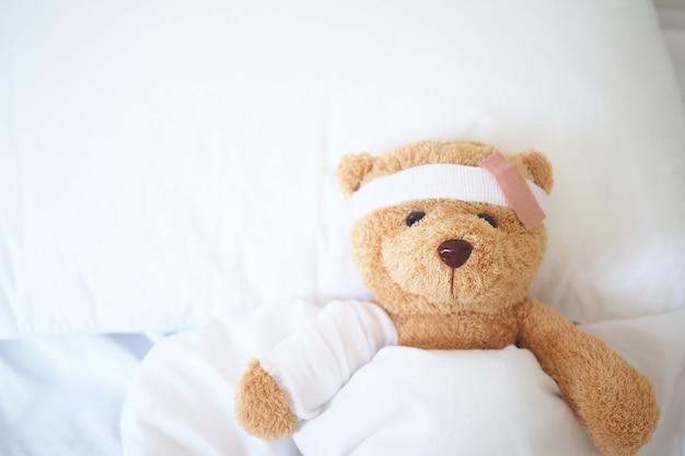 Urso de pelúcia deitado doente na cama com uma faixa de cabeça e um pano coberto Foto Premium