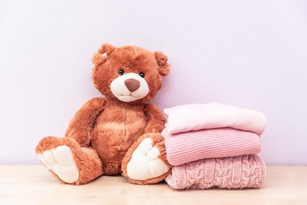 Urso de pelúcia fica perto de uma pilha de roupas femininas de inverno ou outono. Foto Premium